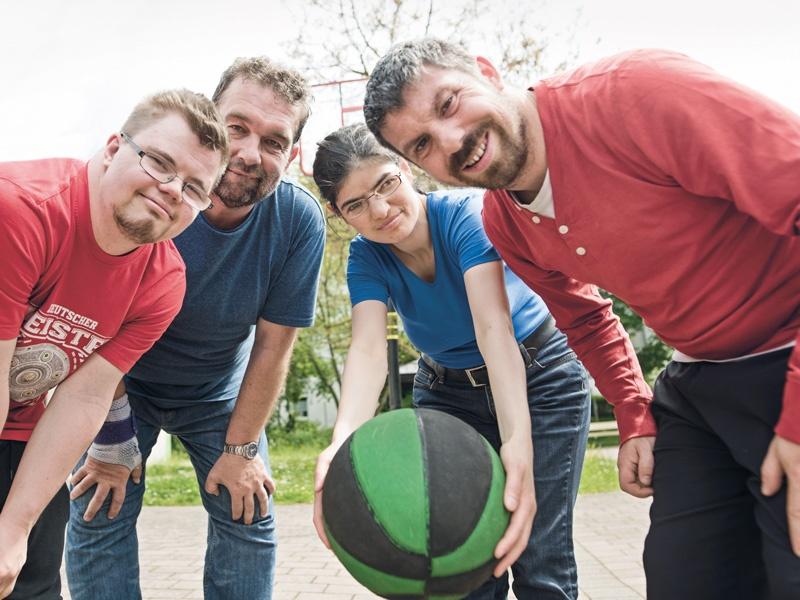 Vier Menschen mit Behinderung beugen sich lächelnd zur Kamera. Die Frau hält einen Basketball.