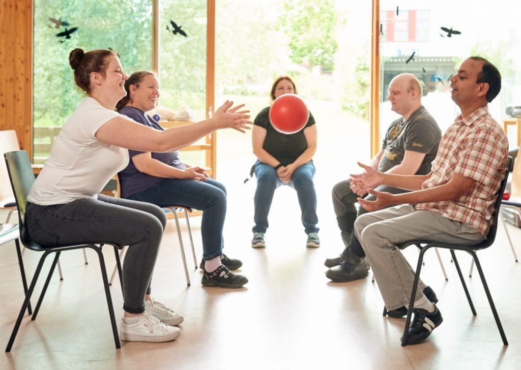 Bewohner*innen des begleiteten Wohnens sitzen in einem Stuhlkreis und werfen sich einen Ball zu.