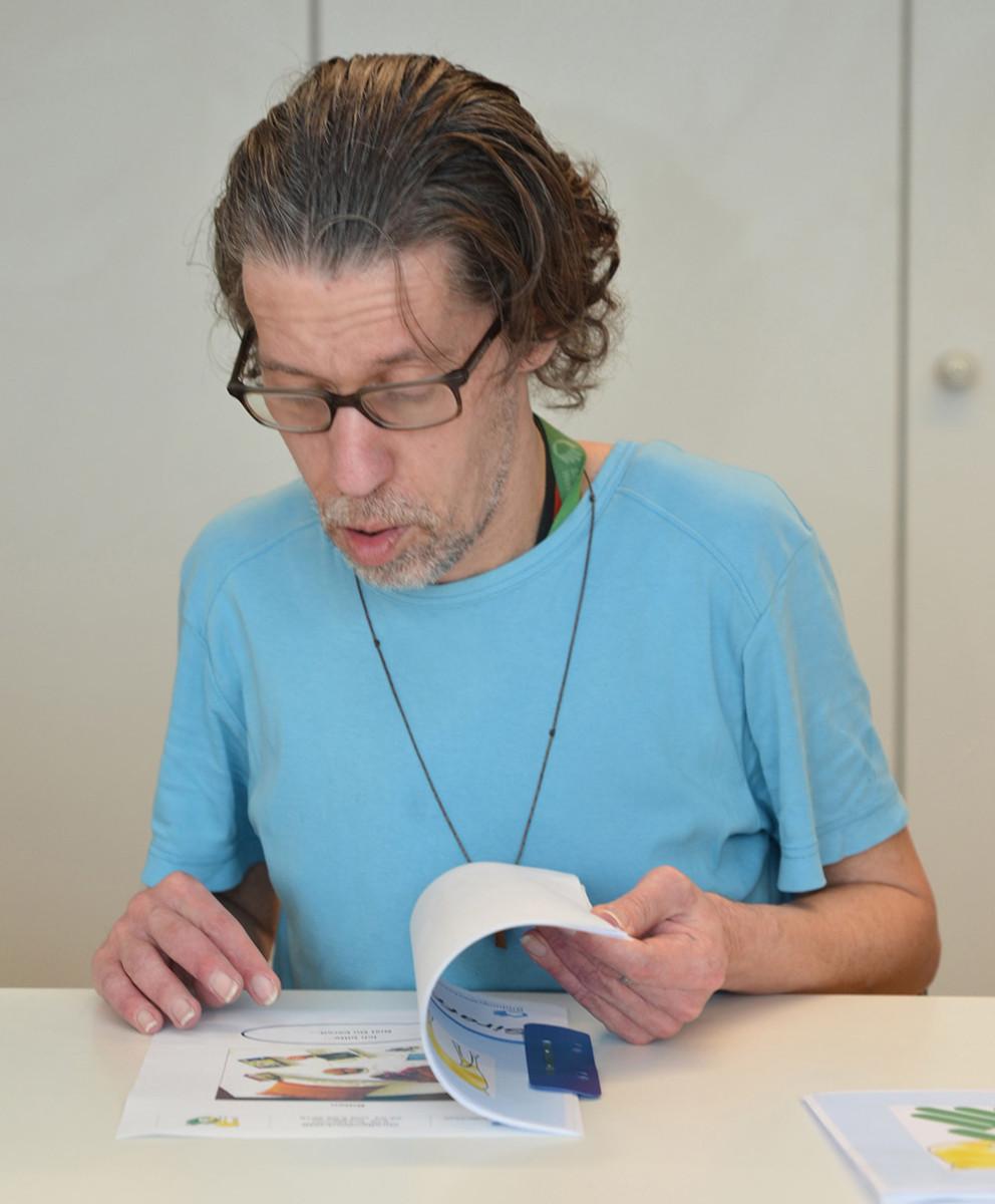 Mann mit Behinderung blättert in einem Heft.
