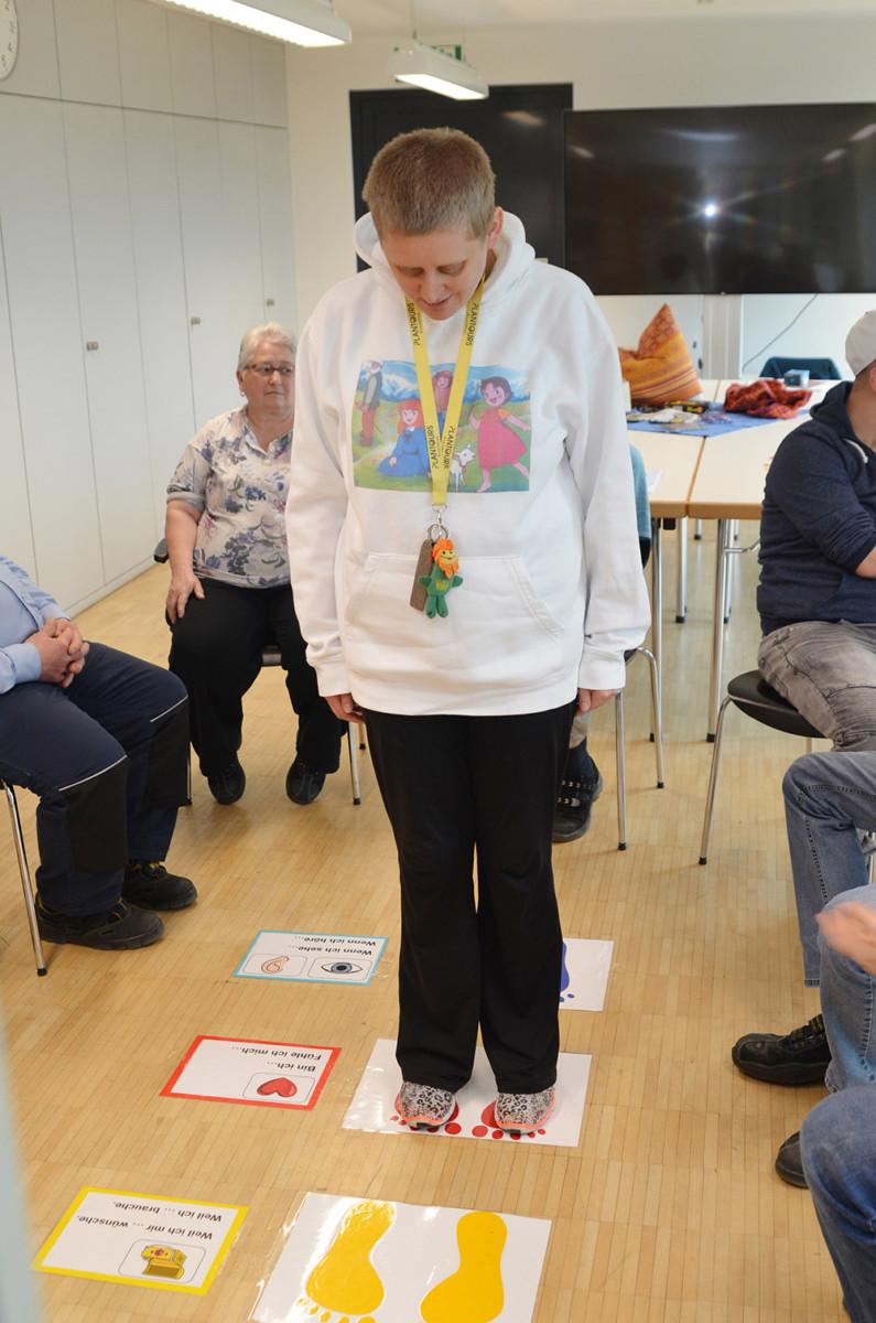 Frau steht in der Mitte eines Stuhlkreises. Auf dem Boden liegen verschiedene Karten und Symbole.