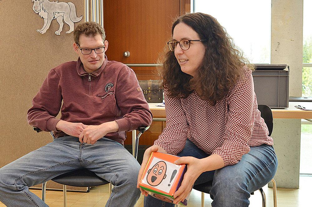 Birgit Eyrisch hält einen Würfel mit abgebildeten Gesichtern
