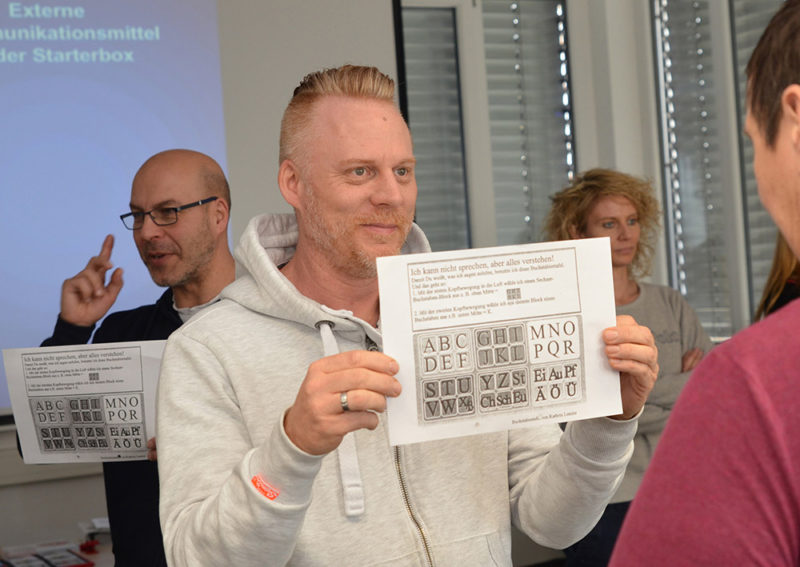 Mann hält ein Blatt mit verschiedenen Buchstaben.