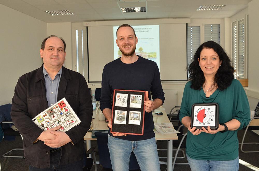 Martina Issler und zwei Mitarbeiter präsentieren verschiedene Materialien, die bei der Kommunikation unterstützen.