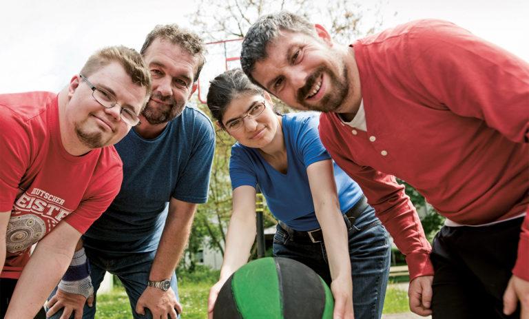 Vier Menschen, zwei mit Behinderung, beugen sich lächelnd zur Kamera. Die Frau hält einen Basketball.